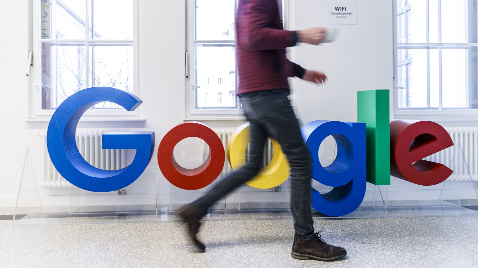 Google logo with man walking in front of it