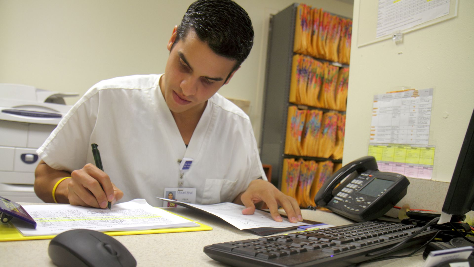 A man at the front desk of a doctors office signs forms