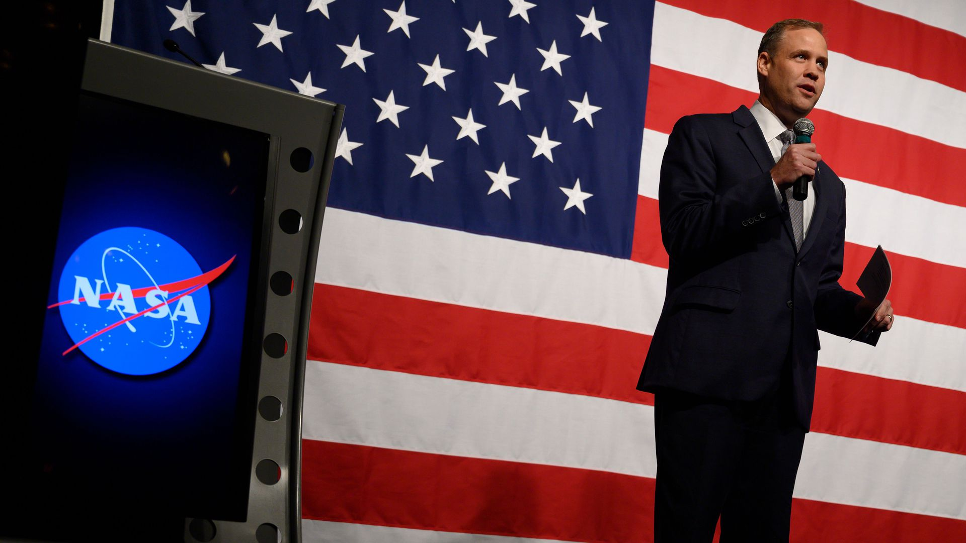 In this image, a man in a suit holds and speaks into a microphone with the American flag behind him.