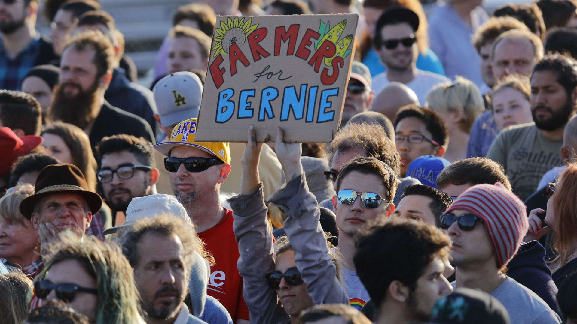 Woman in a crowd holding a farmers for bernie sign