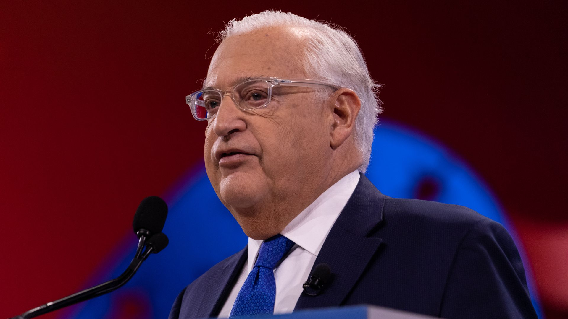 In this image, David Friedman faces the left and speaks, wearing glasses.