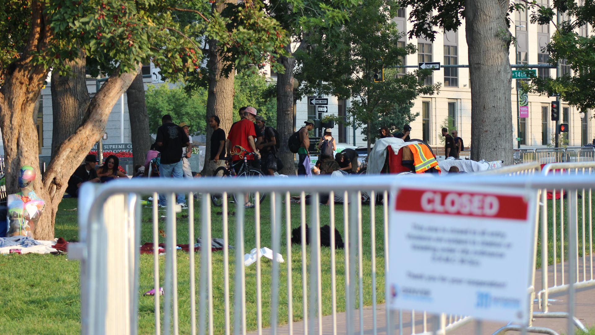 A photo of a park closed sign in the foreground with people experiencing homelessness in the background