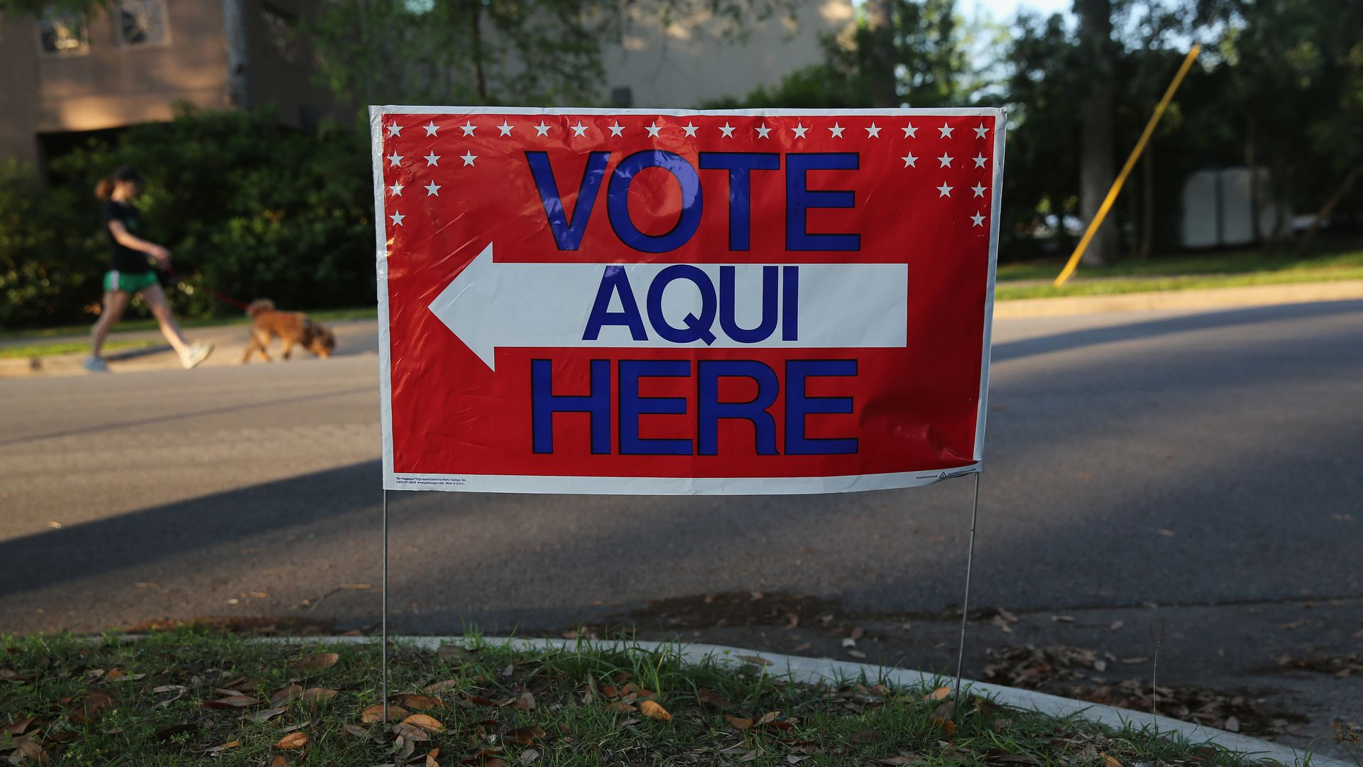 "In this image, a sign reads ""Vote Aqui Here"" on a lawn in a neighborhood."