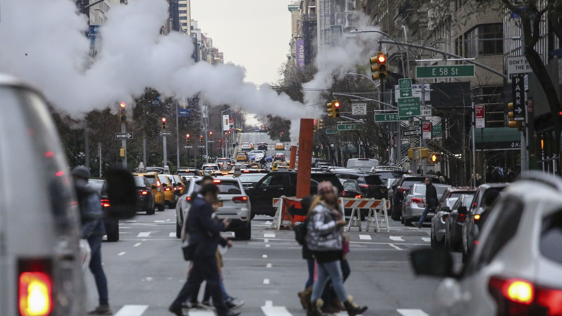 Pedestrians in NYC cross a the street while a pipe emits carbon dioxide emissions