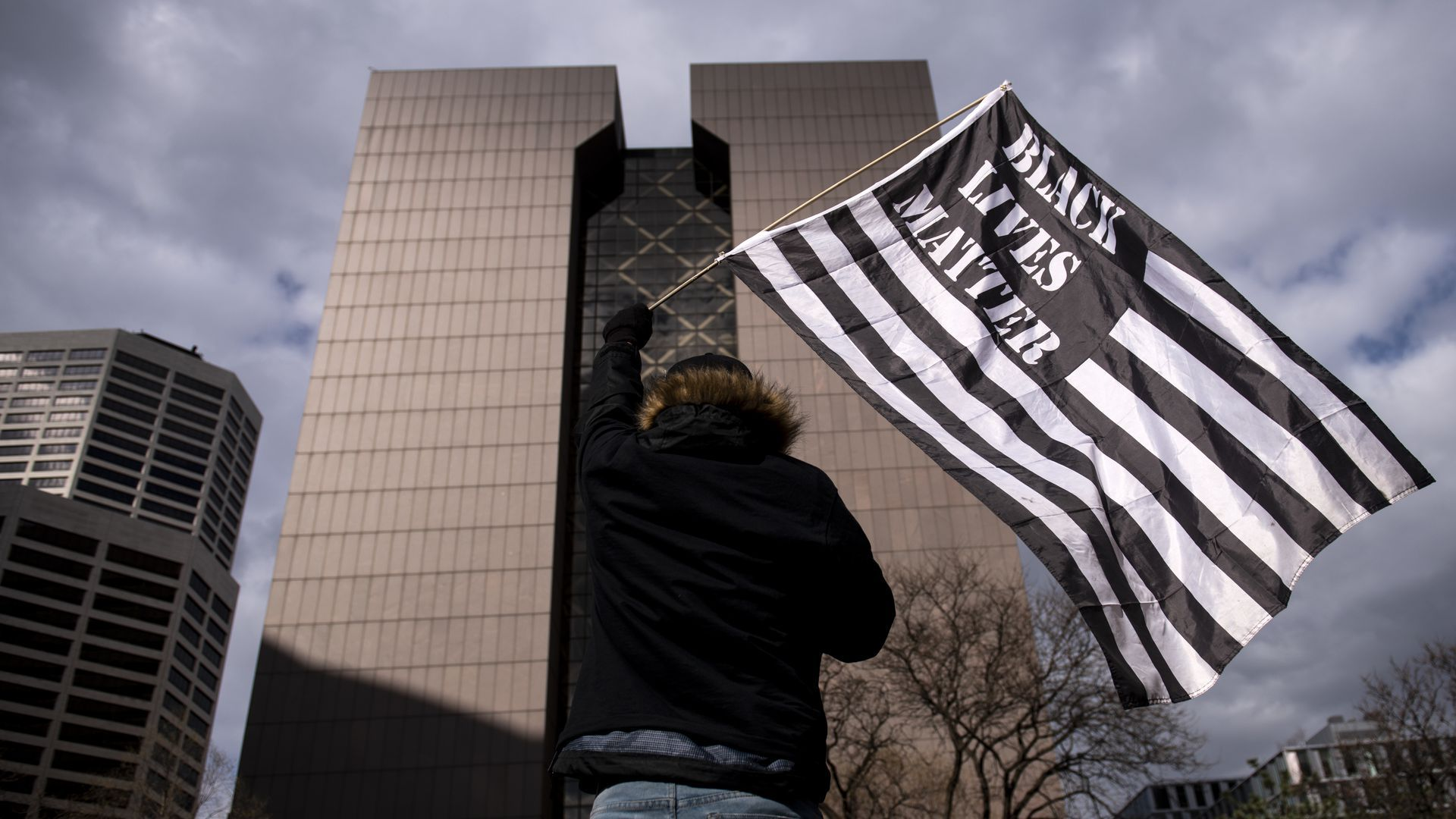 Protester waving flag in front of Hennepin County courthouse