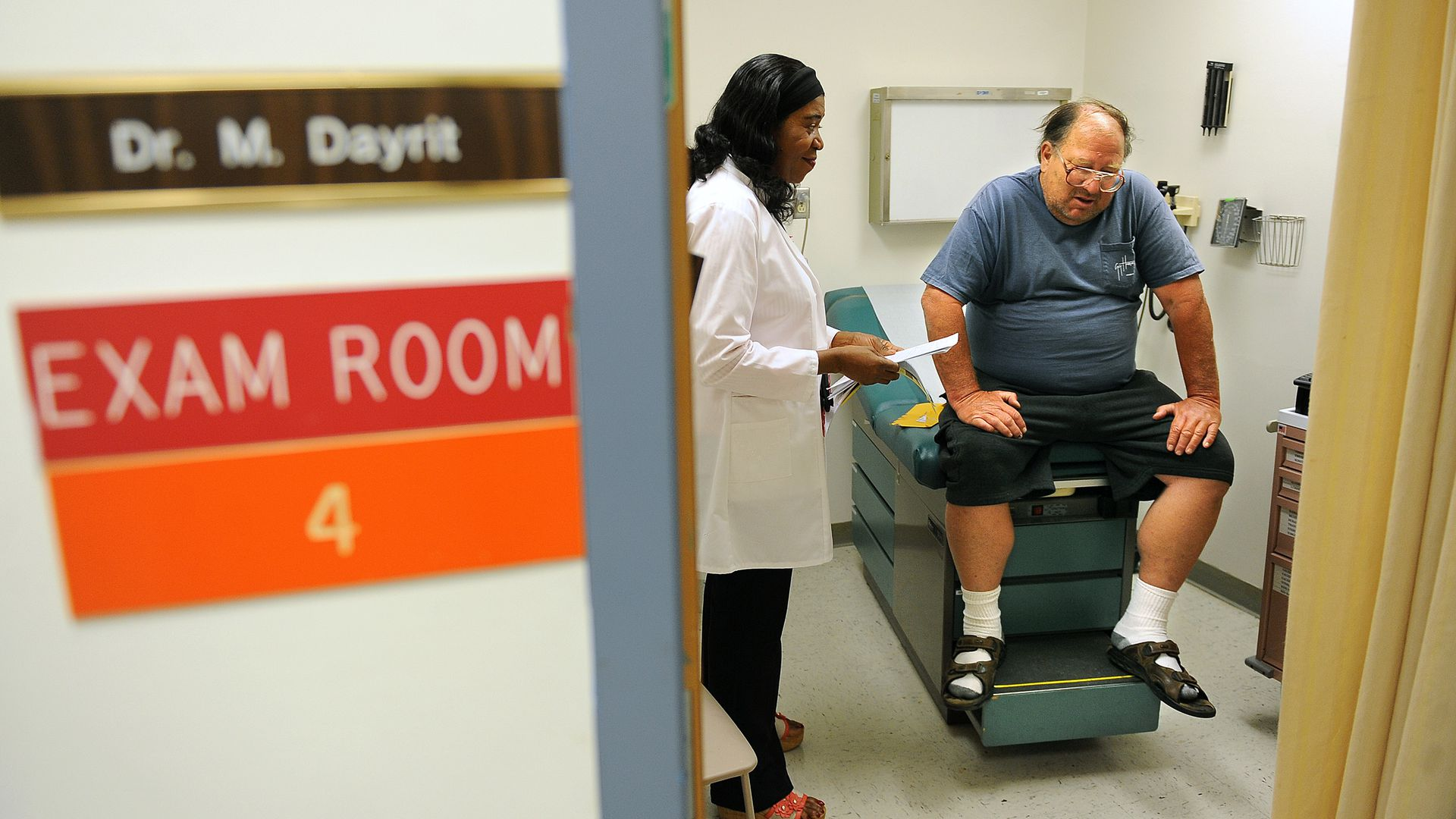 A doctor visits with a patient in an exam room