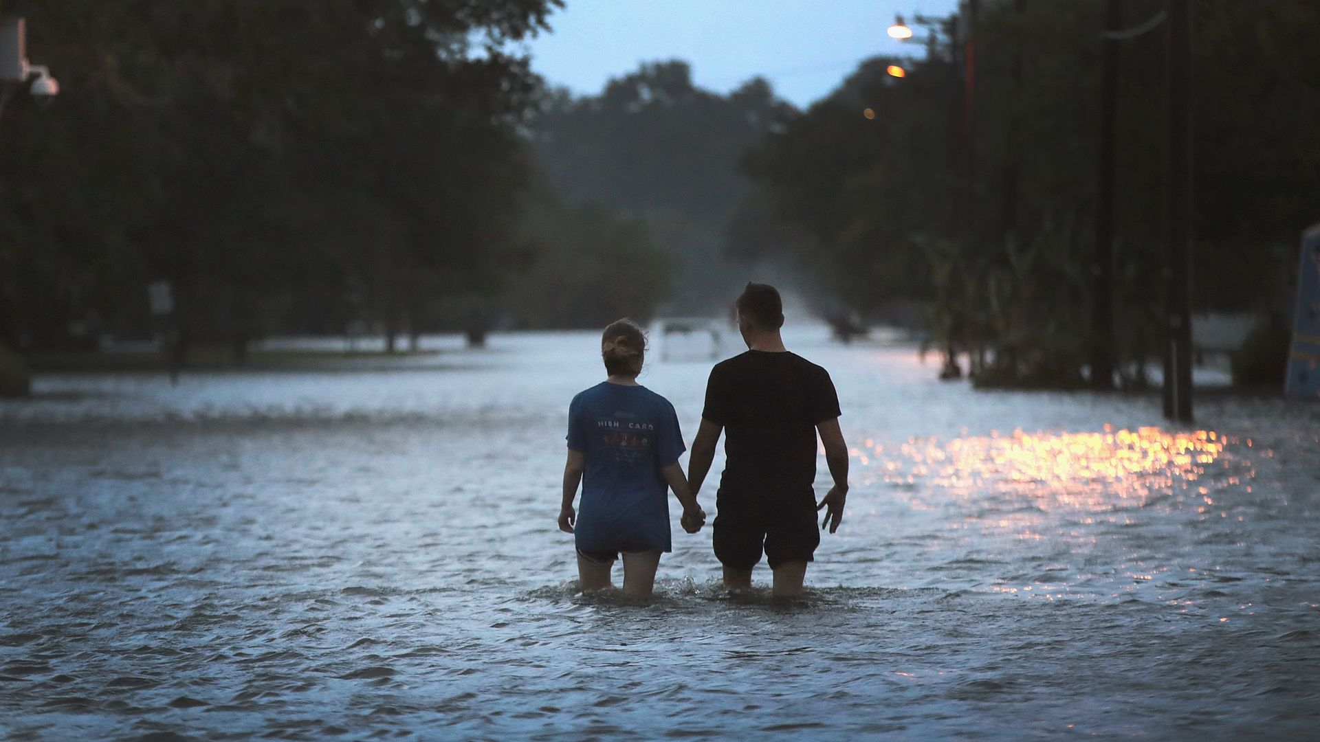 A couple strolls down Lakeshore Drive along the shore of Lake Pontchartrain after it was flooded in the wake of Hurricane Barry on July 13, 2019 in Mandeville, Louisiana.