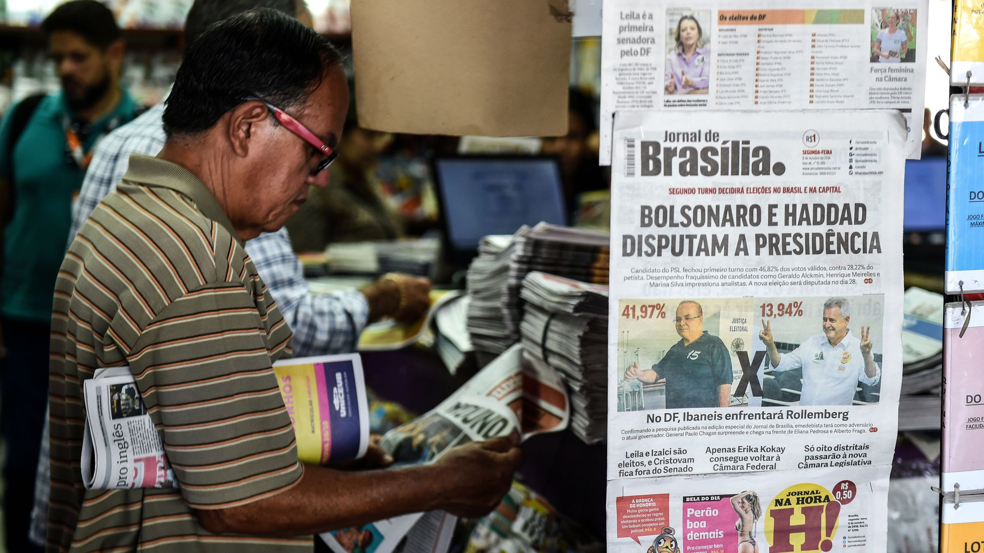 mans looking at newspapers at Brazilian newsstand