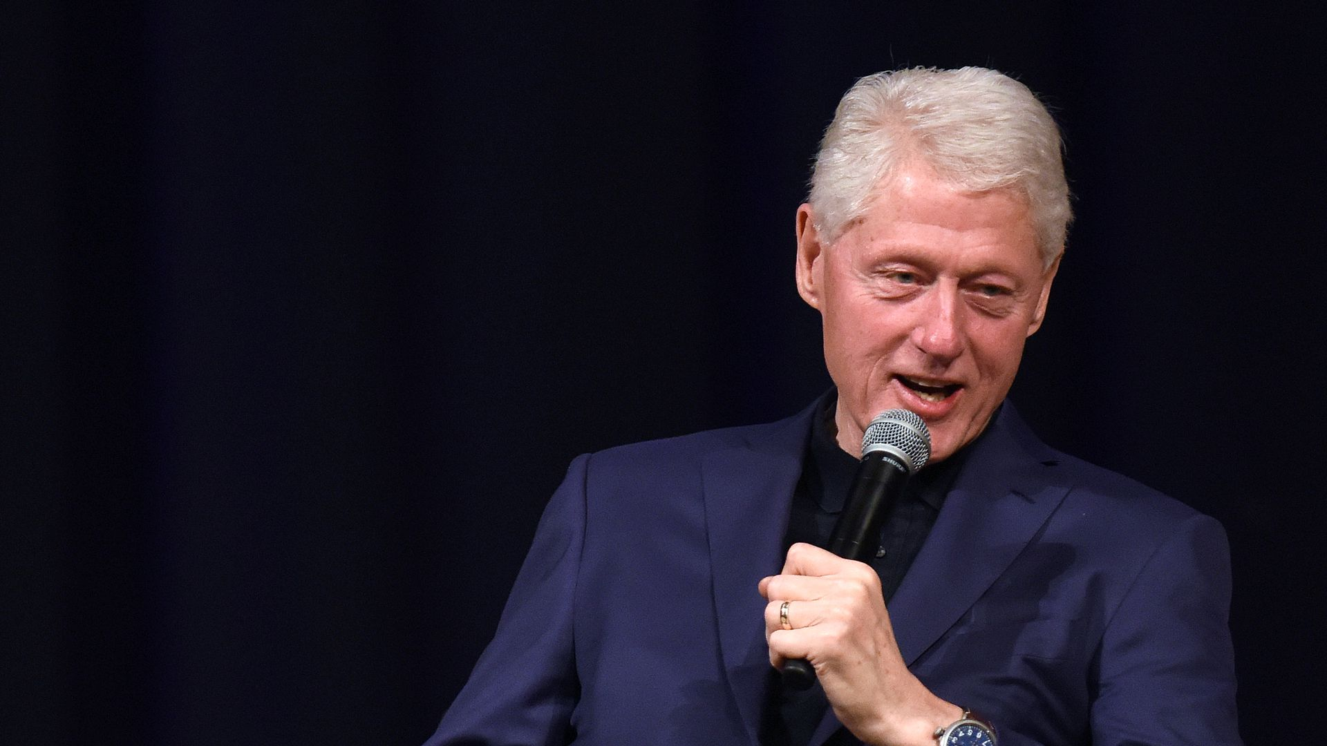 Bill Clinton speaks with a microphone.