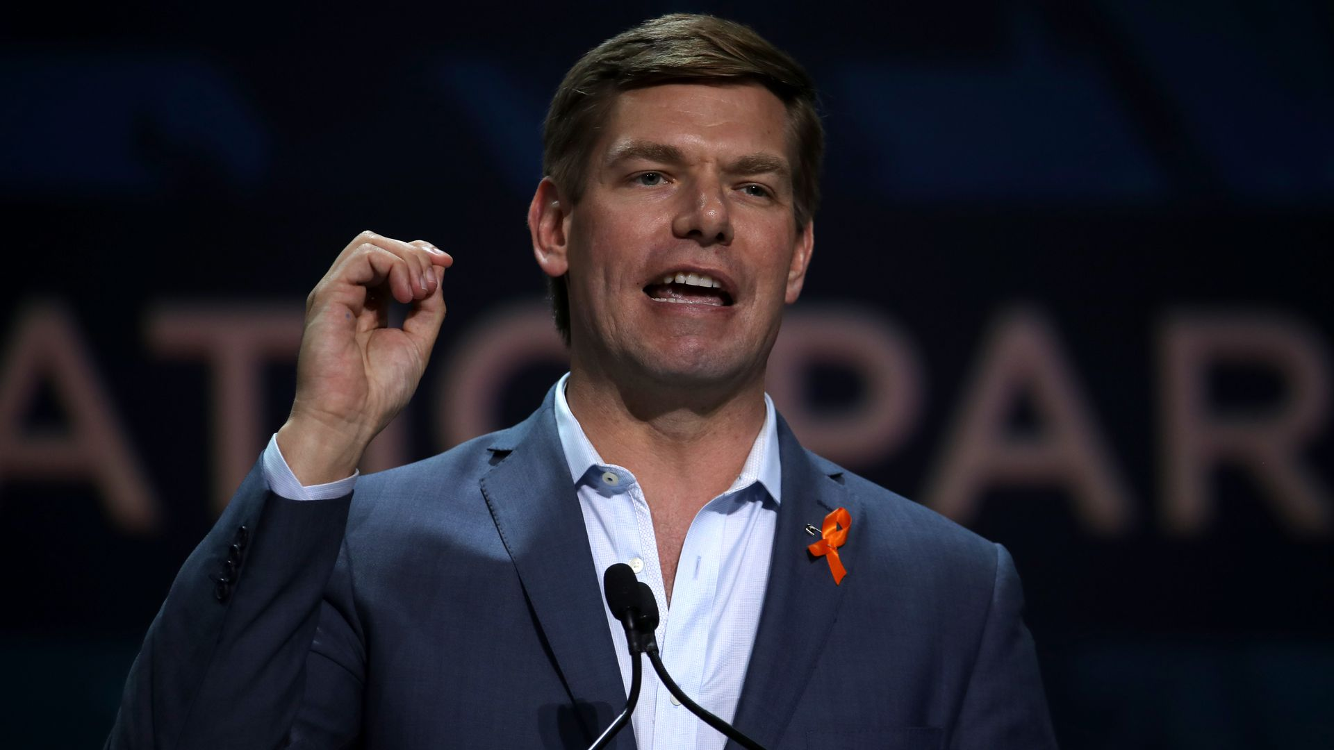 Eric Swalwell standing on stage and speaking into a microphone.