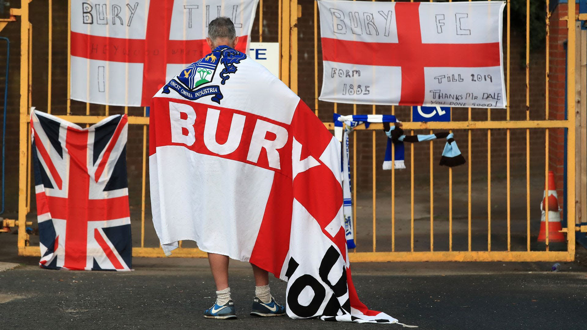 A man standing in front of the now closed English soccer club Bury FC