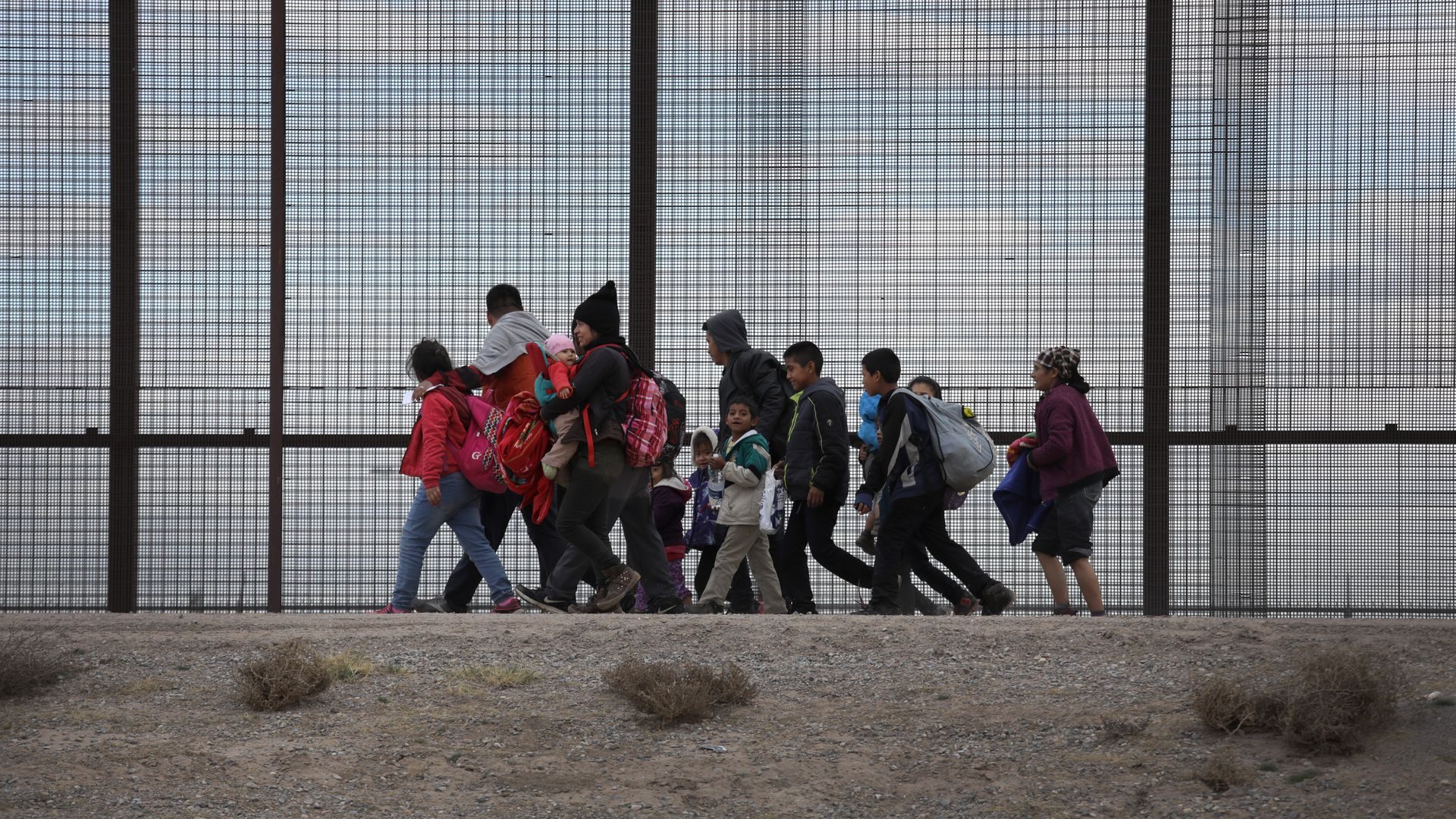 Migrants at the border fence.