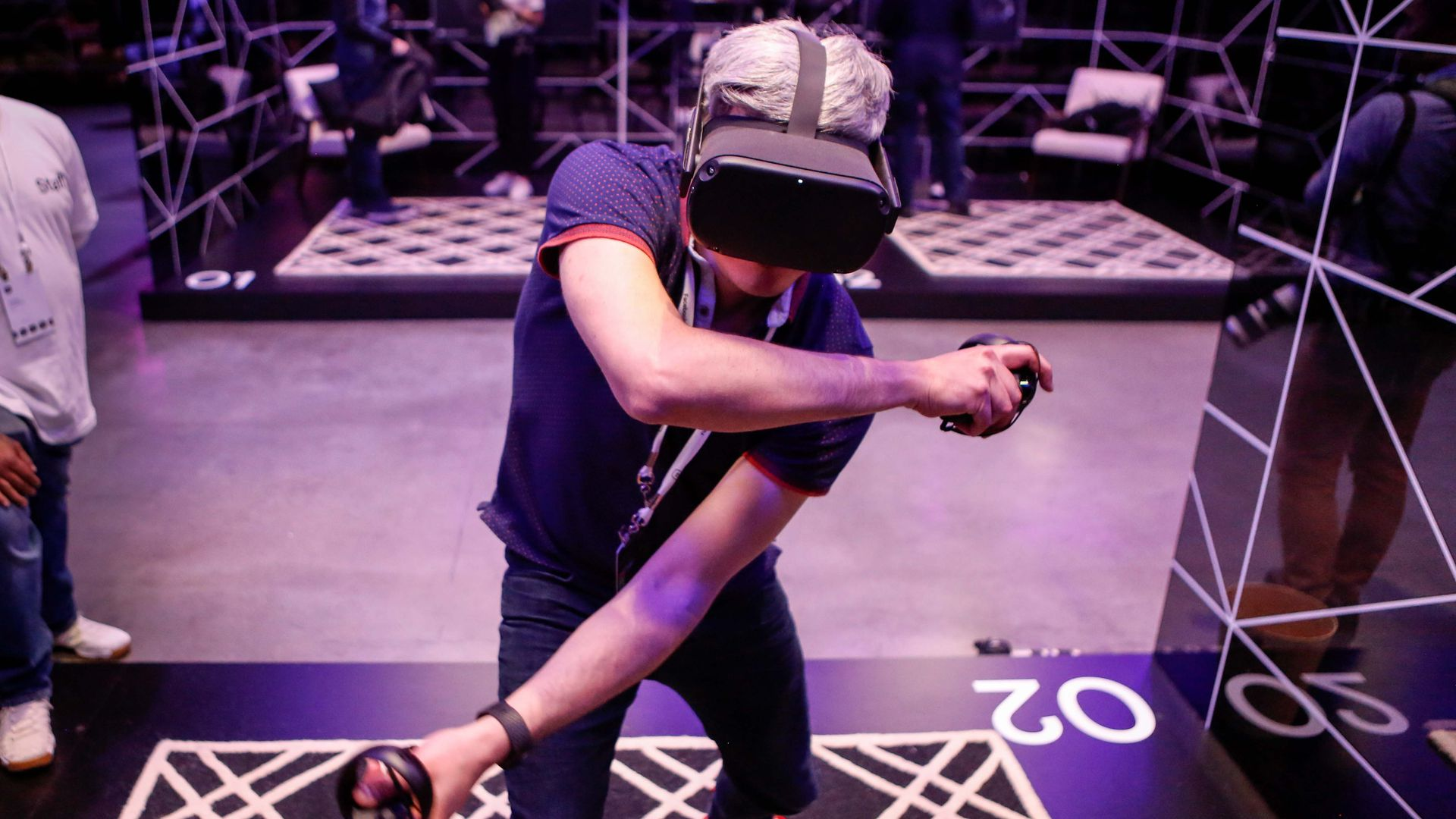 Photo of a person wearing a VR headset and gesticulating with two controllers