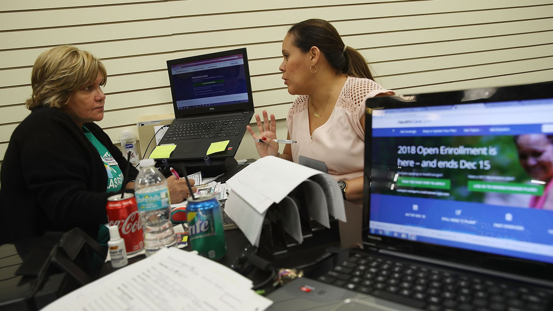 A health insurance broker helps a woman sign up for health insurance.