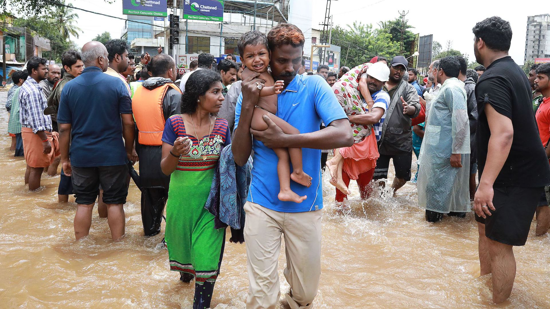 Indian volunteers and rescue personal evacuate local residents in a residential area at Aluva in Ernakulam district, in the Indian state of Kerala, on August 17, 2018.