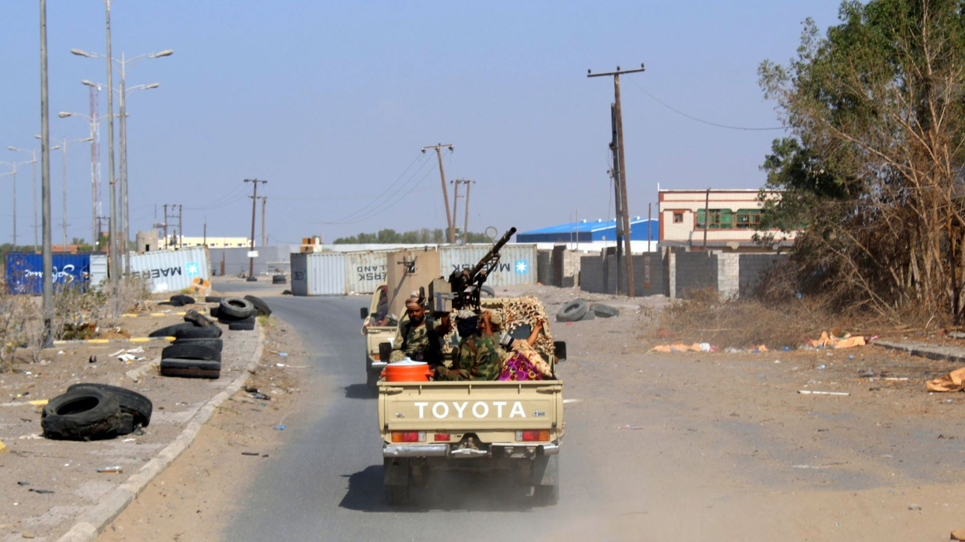 Yemeni government fighters in a truck on an empty, dusty road