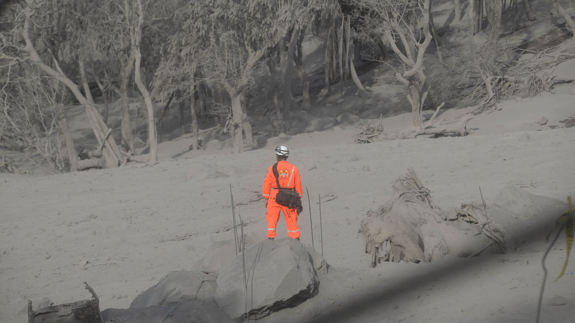A firefighter standing in an area covered by ash after the eruption of the volcano.