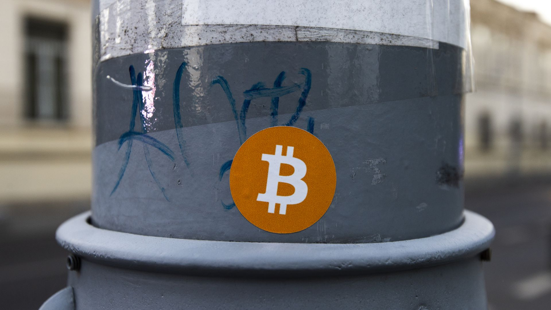 A sticker with the Bitcoin logo on it, on a lamp post.