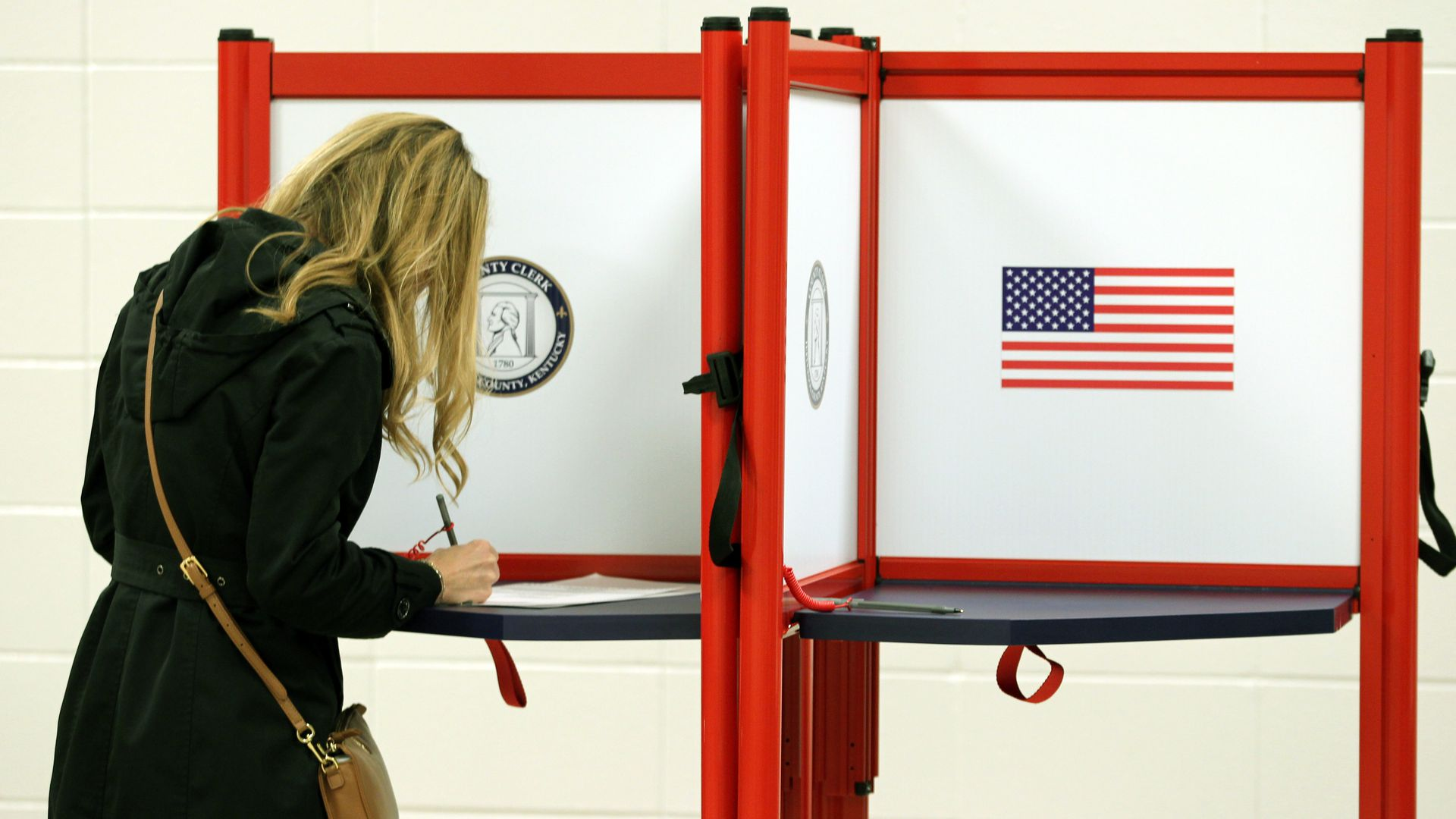 In this image, a woman leans over a voting booth