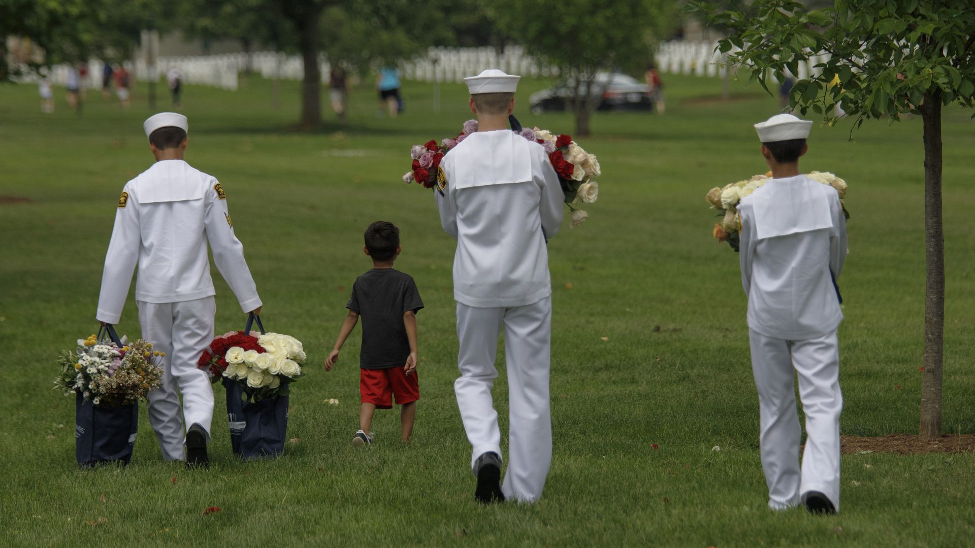United States Naval Sea Cadets carry flowers to Cemetery Section 33, during a volunteer event ahead of Memorial Day at Arlington National Cemetery