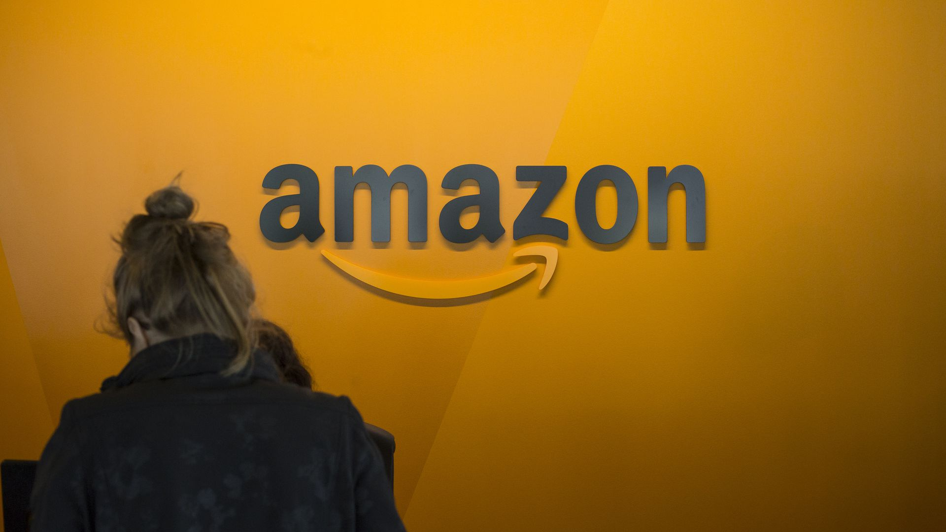 A woman walks in front of an orange wall with the Amazon.com logo on it
