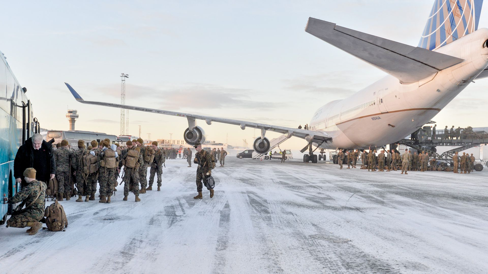 U.S. Marines disembark fro a plane onto a snowy tarmac.