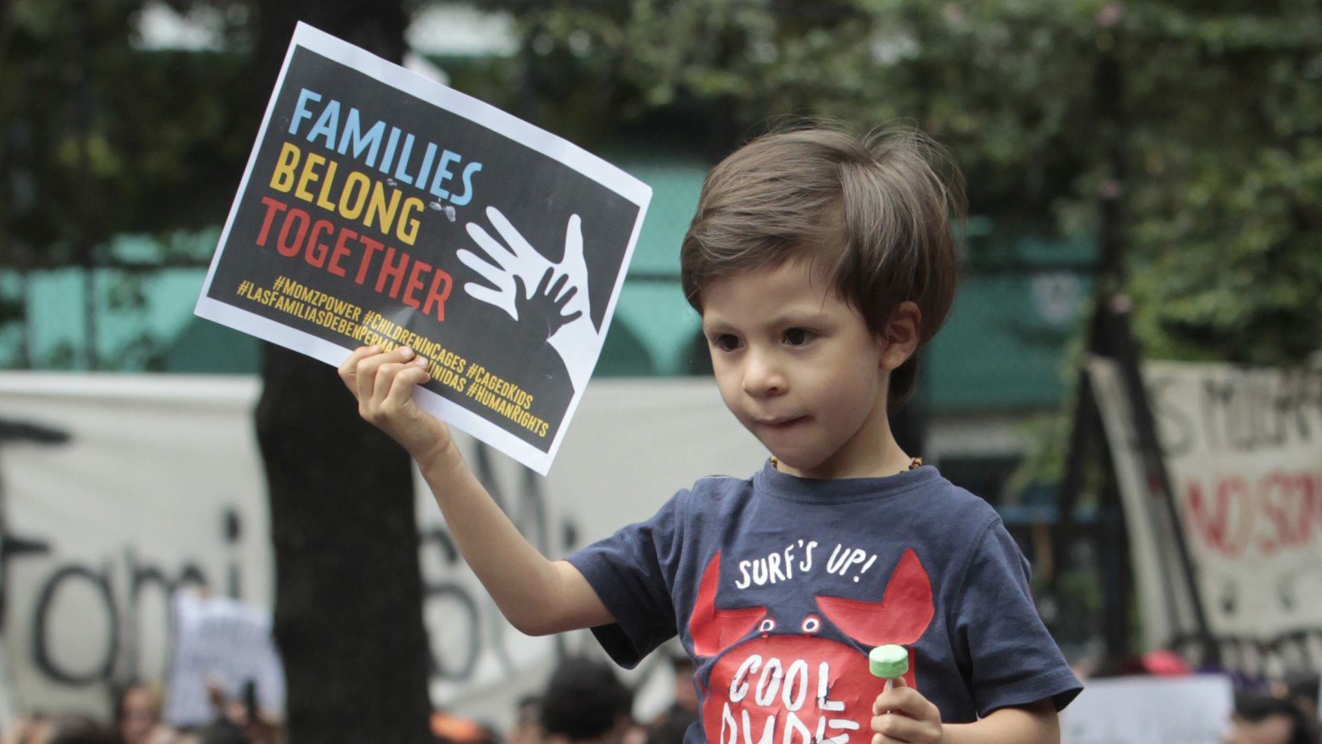 "A child holds a sign that reads, ""Families Belong Together,"" during a protest of family separation."