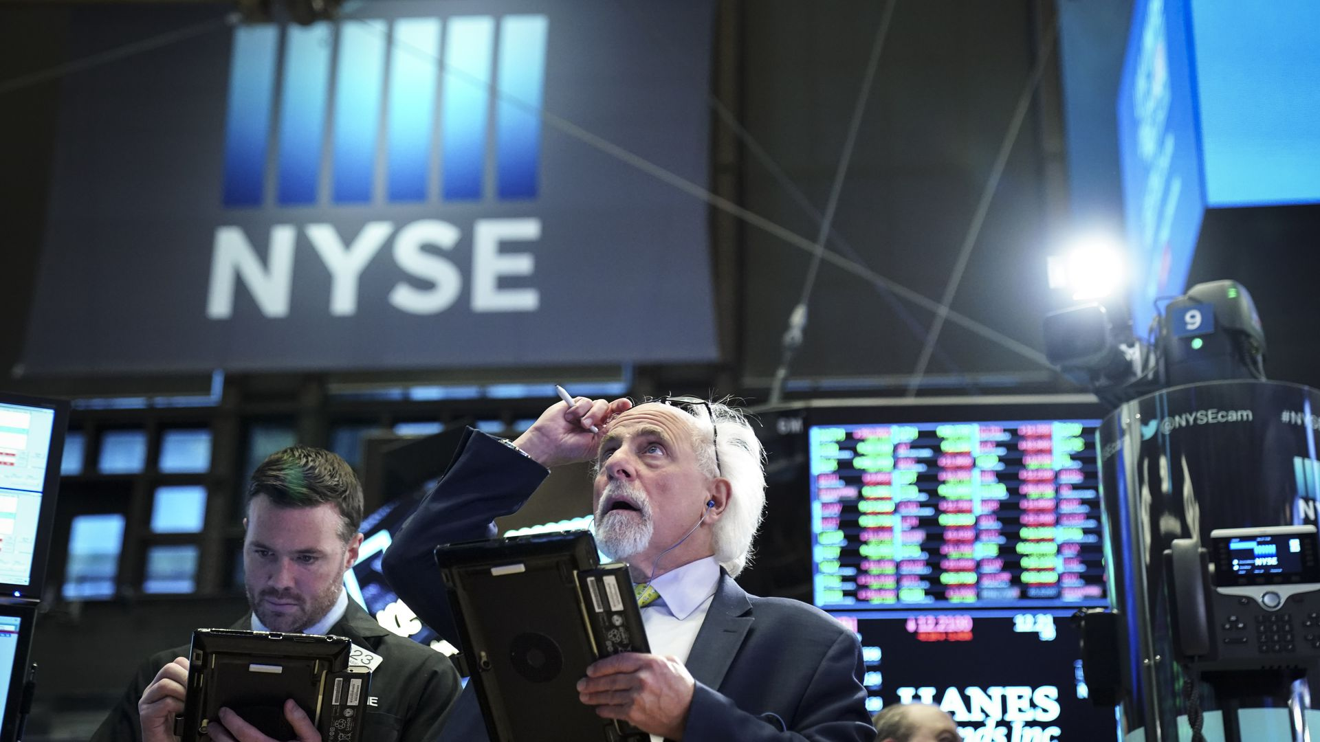 Two traders look at trading screens on NYSE floor.