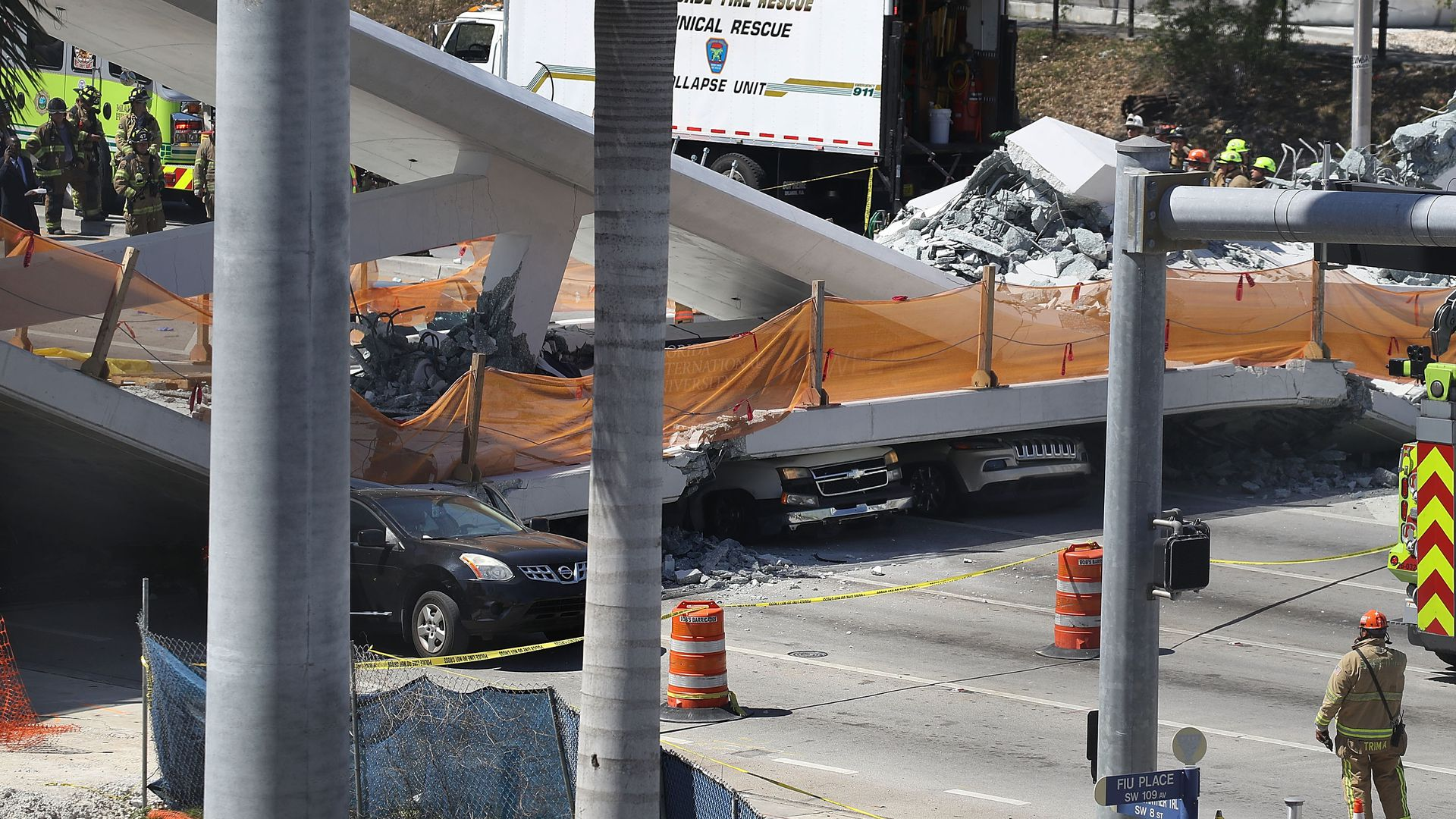 Vehicles are seen trapped under the collapsed pedestrian bridge.