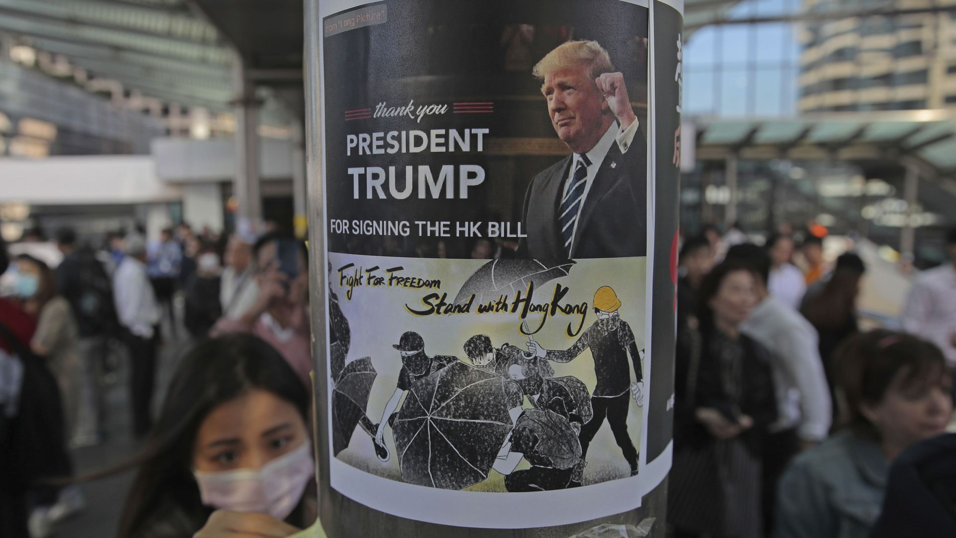 A pro-democracy protester sticks a poster featuring President Trump on a pillar in the Hong Kong financial district today