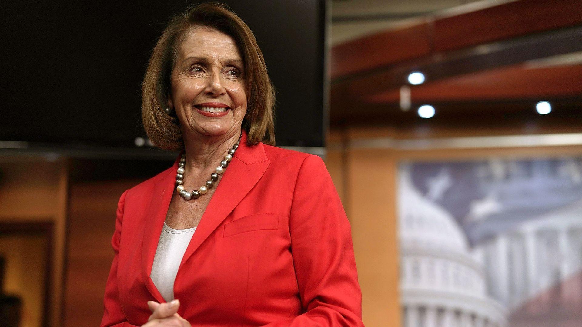 Nancy Pelosi wearing a red pantsuit
