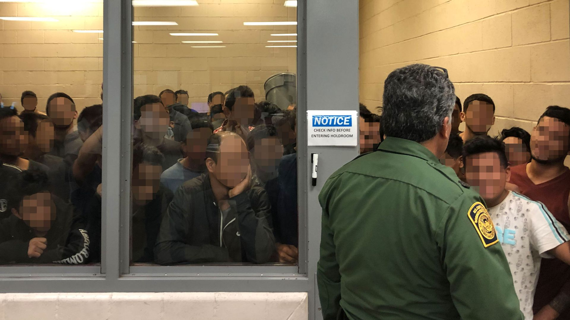In this image, a CBP officer stands in front of a room of detained migrants