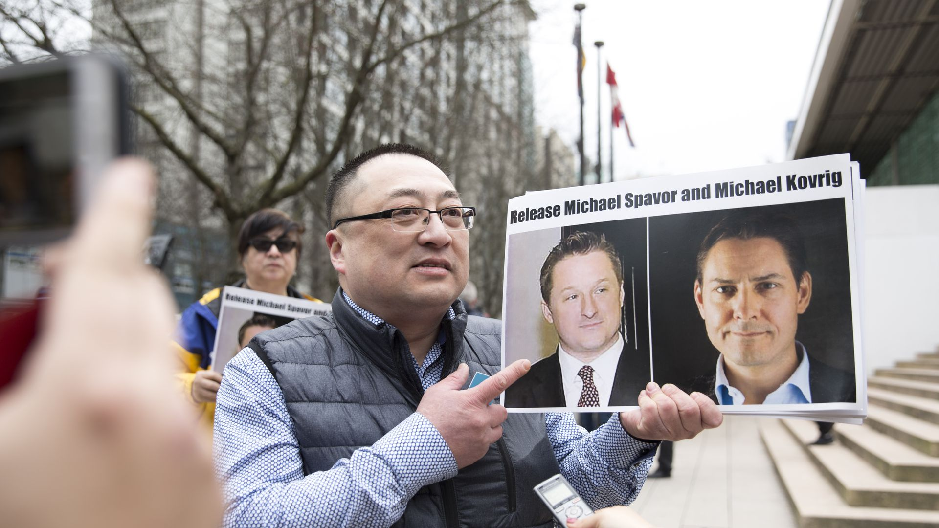 Louis Huang of Vancouver Freedom and Democracy for China holds photos of Canadians Michael Spavor and Michael Kovrig.