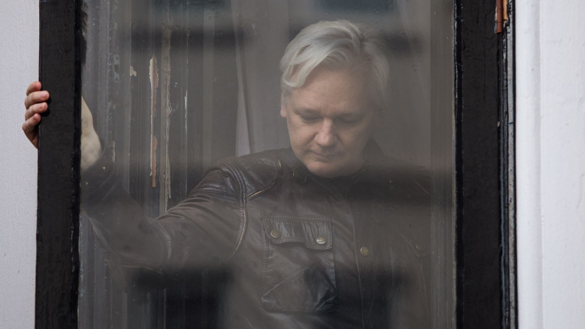 Julian Assange seen through a window, looking down.