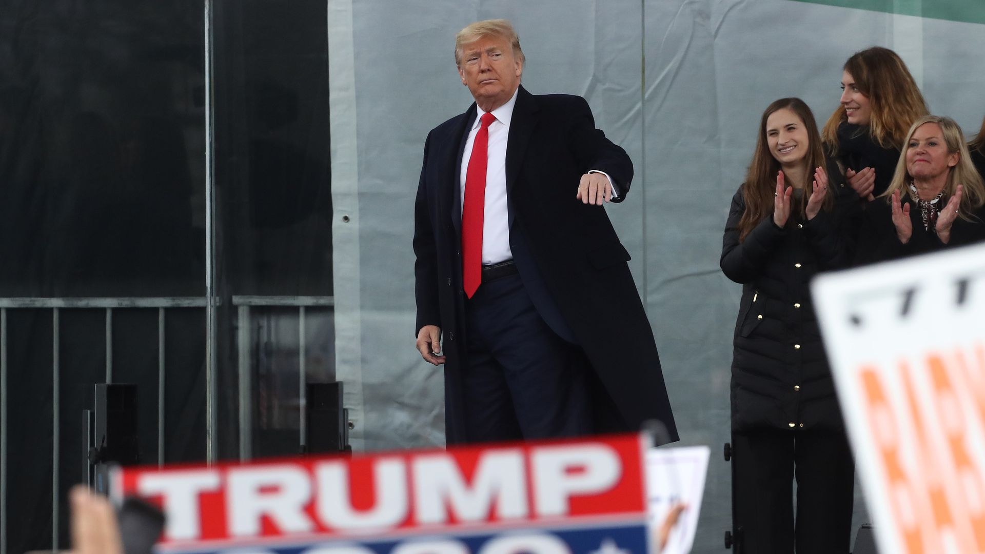 Trump stands in front of a crowd.