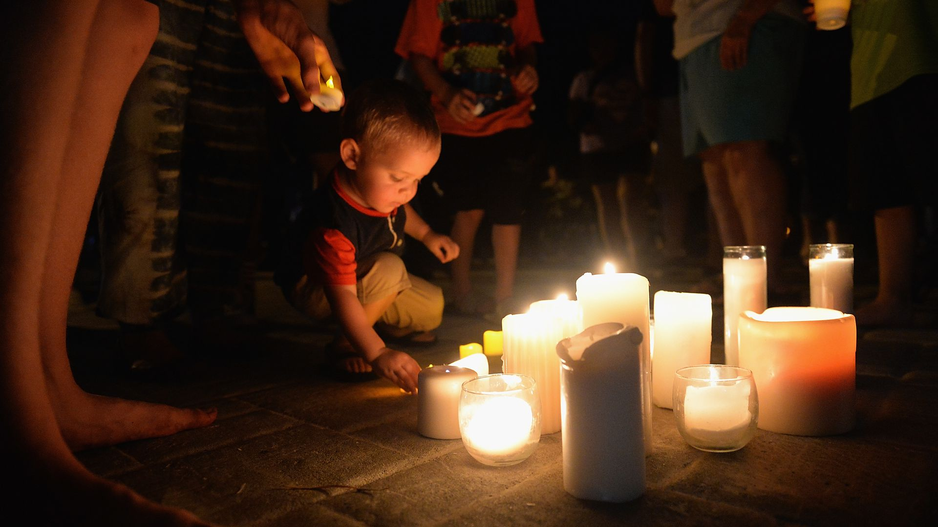 A child places a candle on the floor during a vigil.