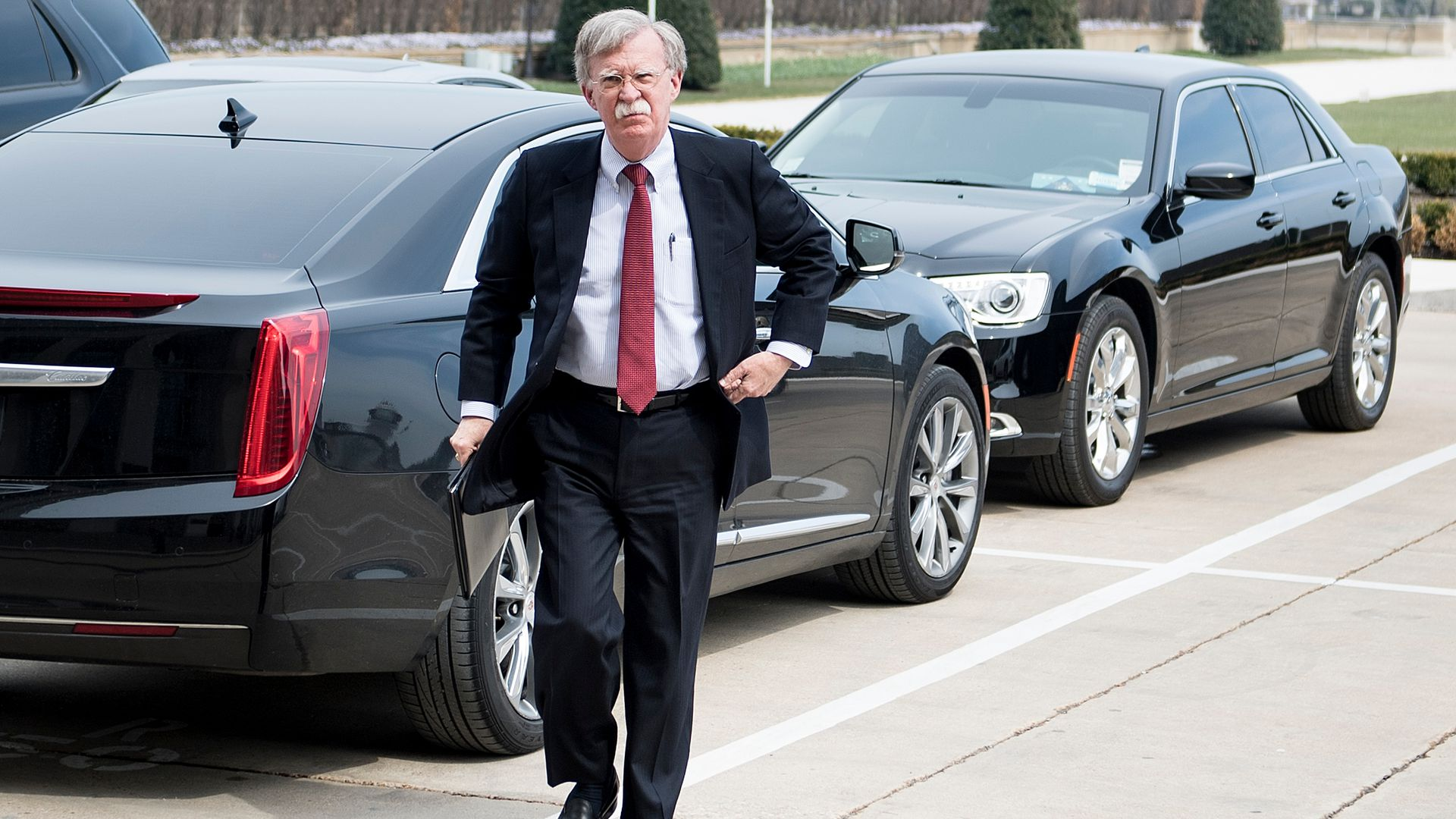 John Bolton in front of black cars