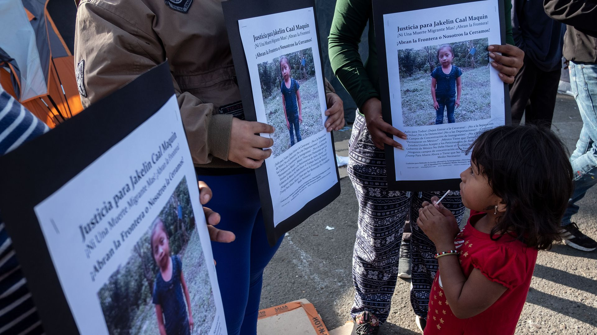 In this image, a child stands in front of demonstrators who hold white text descriptions of missing persons.