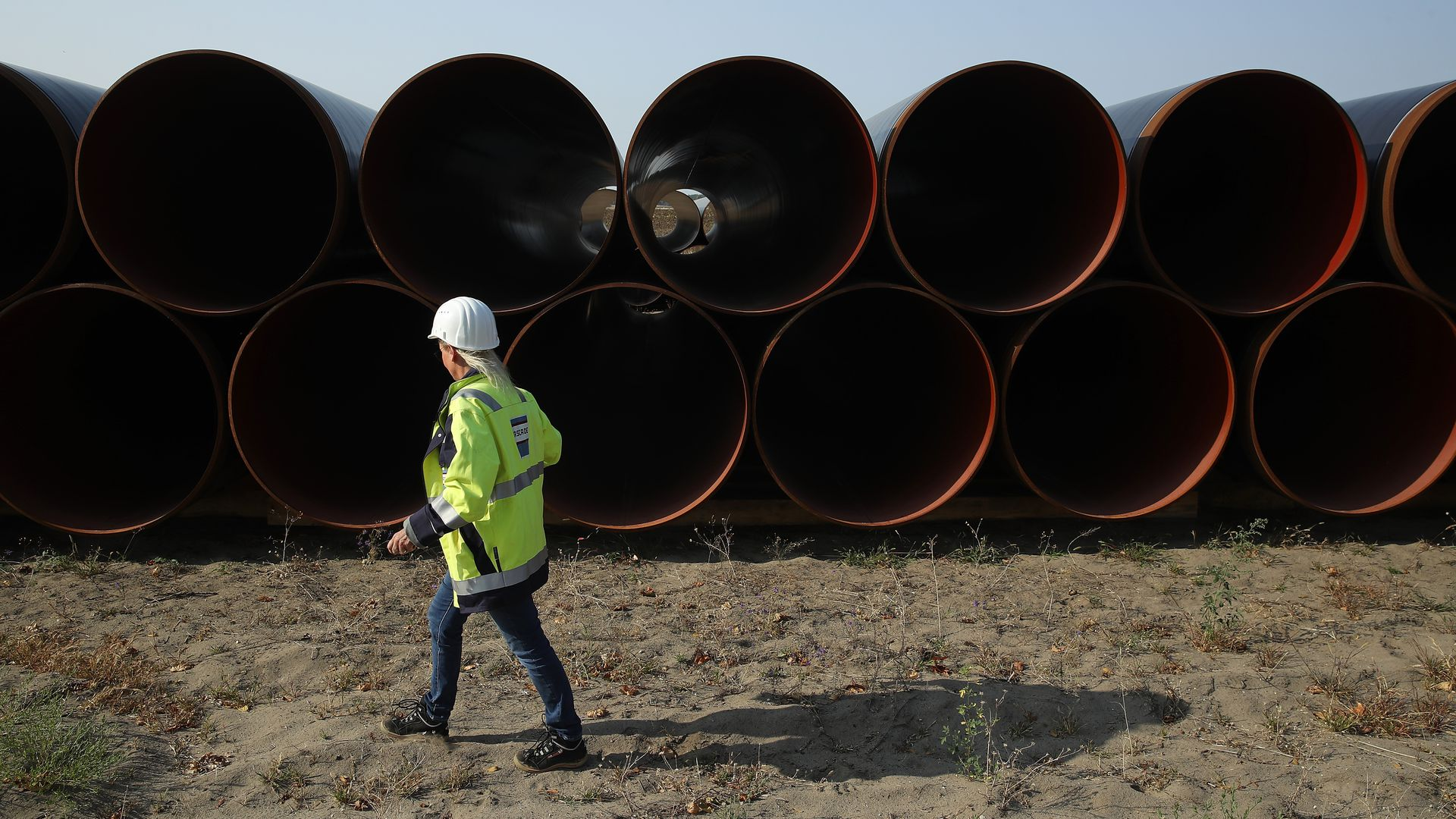 An employee of GASCADE Gastransport GmbH walks among sections of steel pipe stacked ahead of construction of the Eugal natural gas pipeline