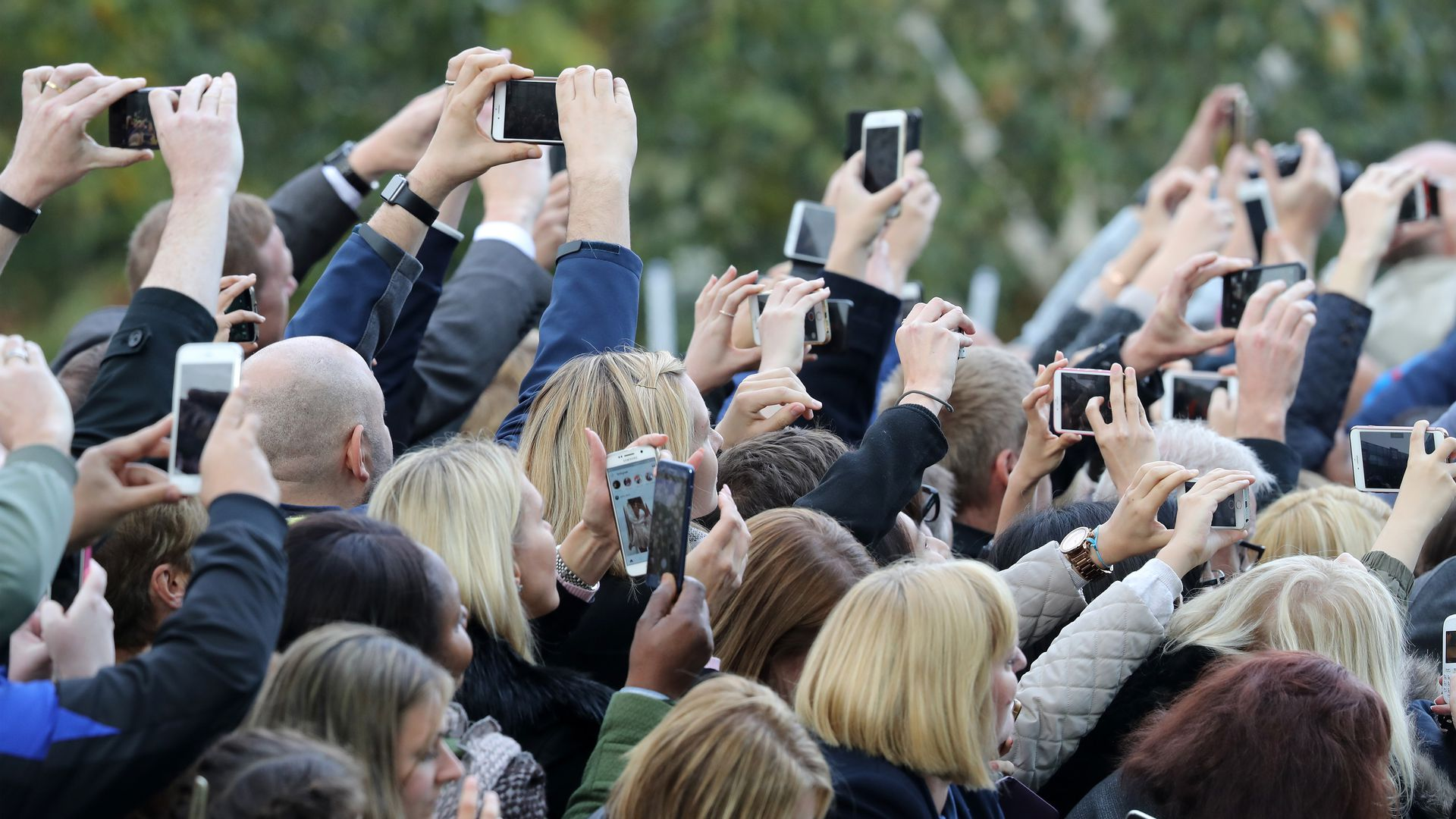A group of people use cell phones to take pictures of Prince William