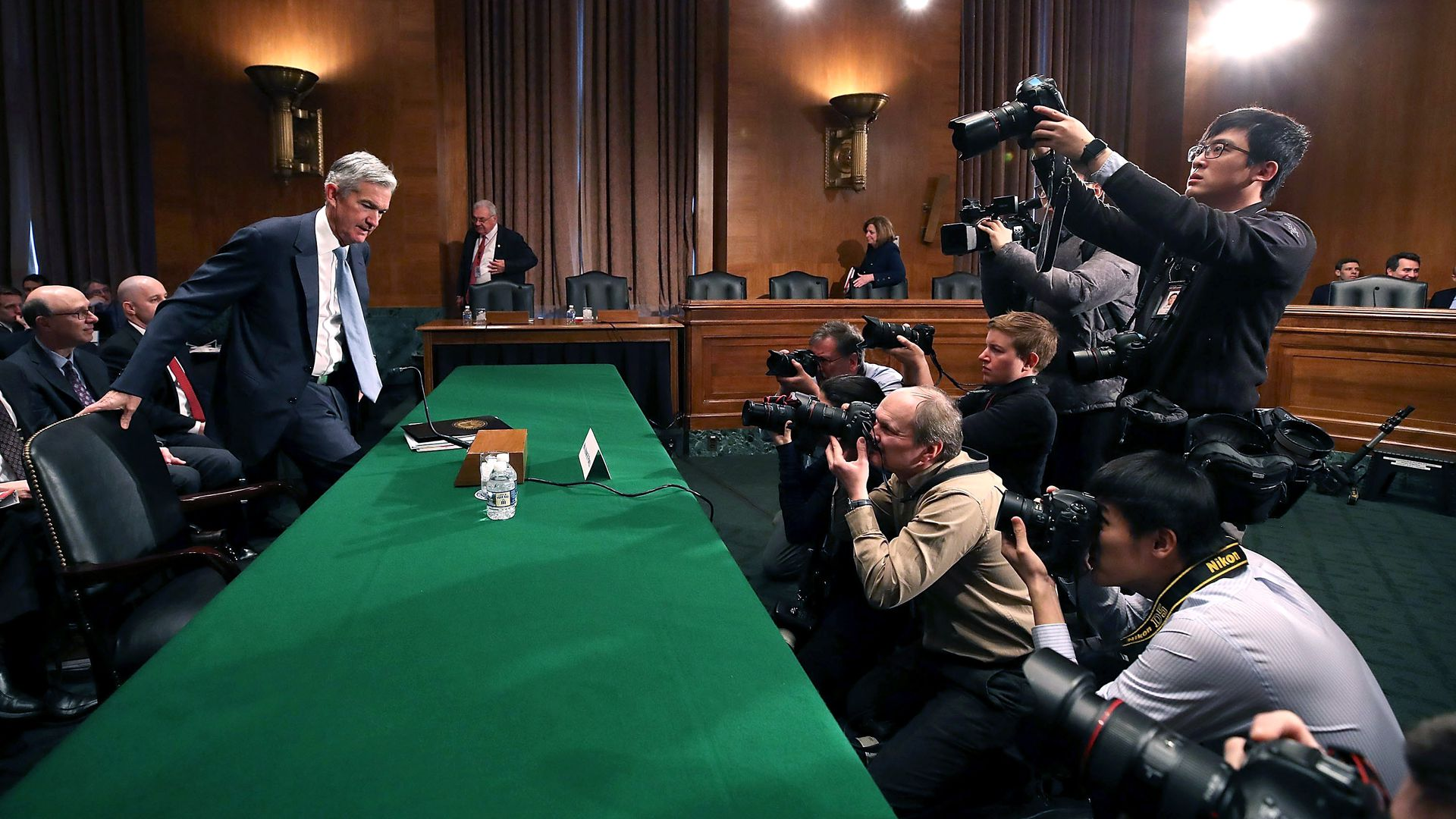 Fed Chair Jerome Powell sits down at a large green table as photographers snap pictures.