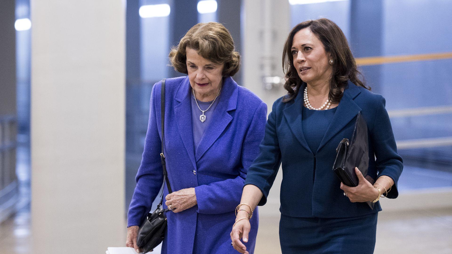 Senators Dianne Feinstein and Kamala Harris walking side by side in the Capitol building