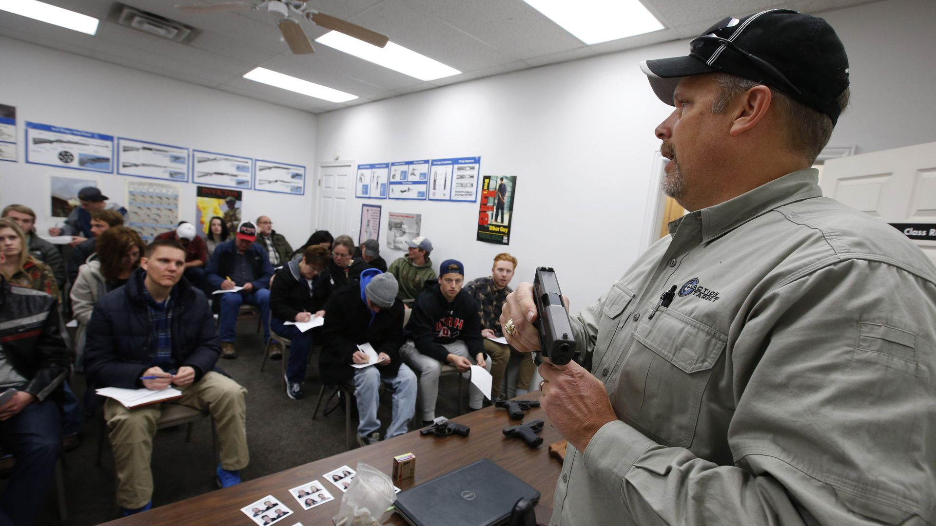 Gun instructor Mike Stilwell, demonstrates an semi automatic hand gun as as he teaches a packed class in Utah.