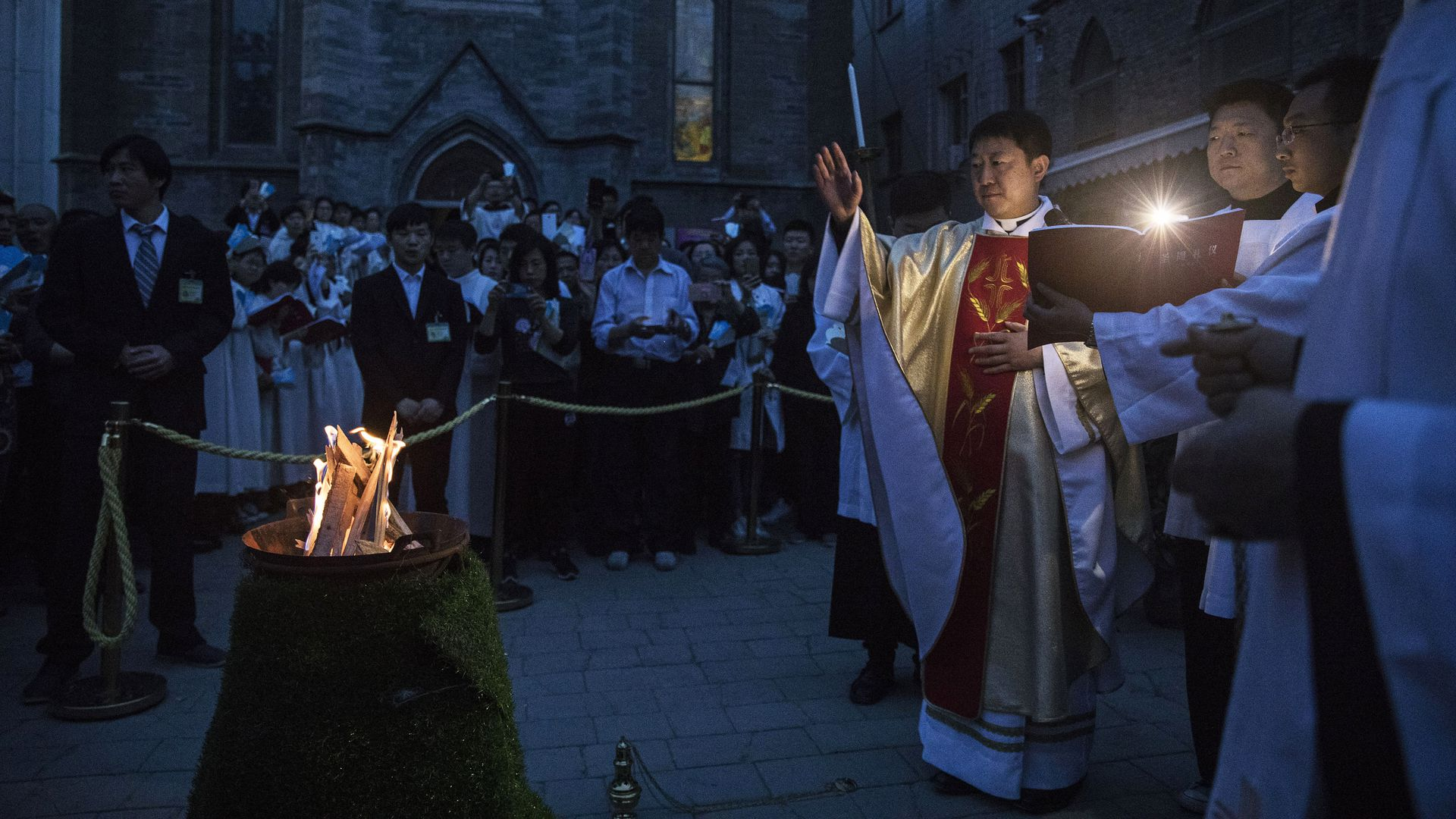 Chinese Catholic Bishop Zhang Hong blesses the flame used to light the Paschal Candle at a mass during Easter celebrations in 2017 in Beijing.