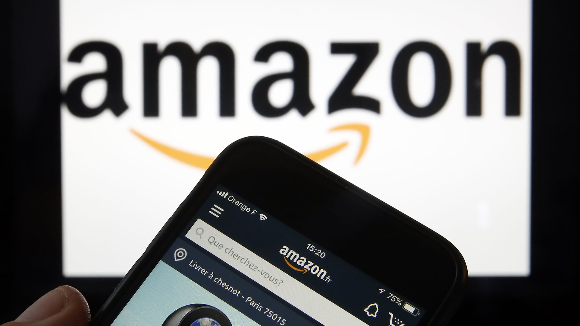 Amazon's logo in the background with the Amazon website on a phone in the foreground.