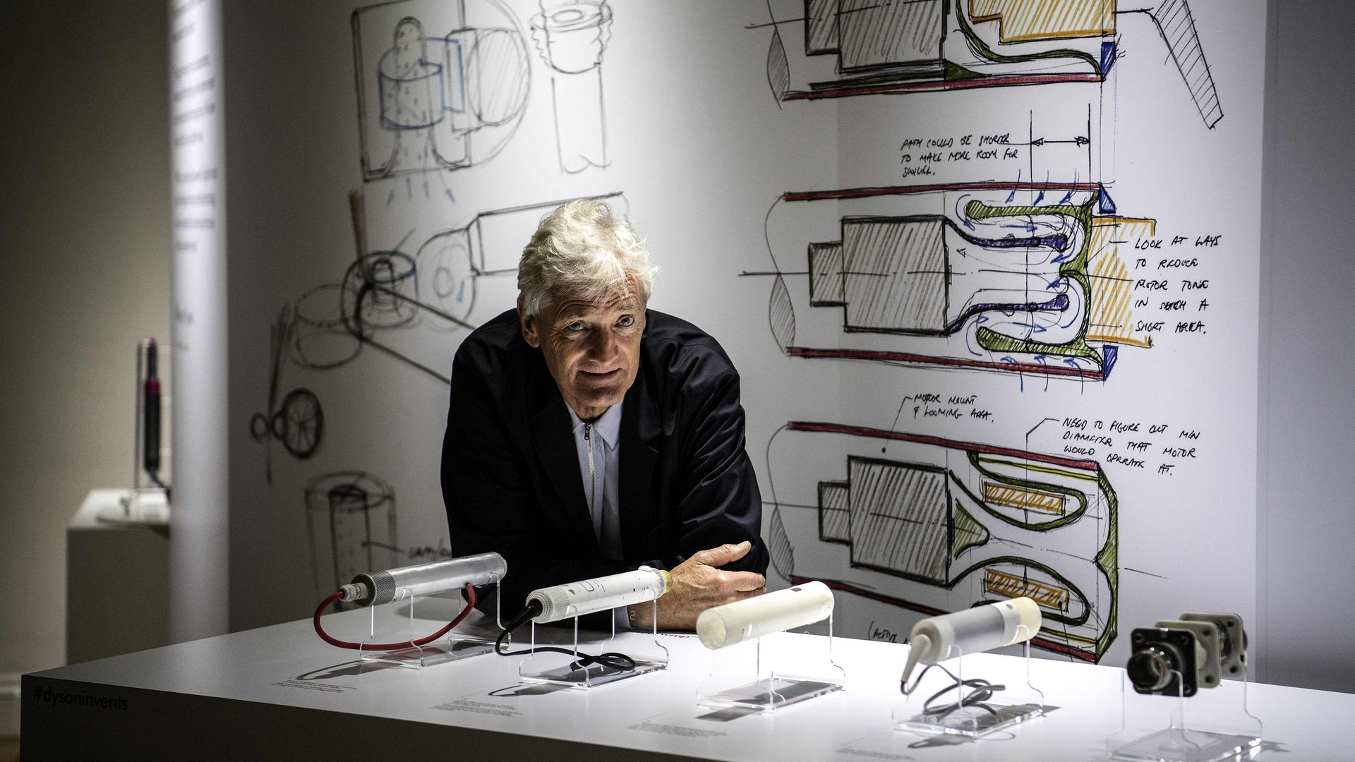 Dyson ceo leaning on a table with blueprints of vacuums.