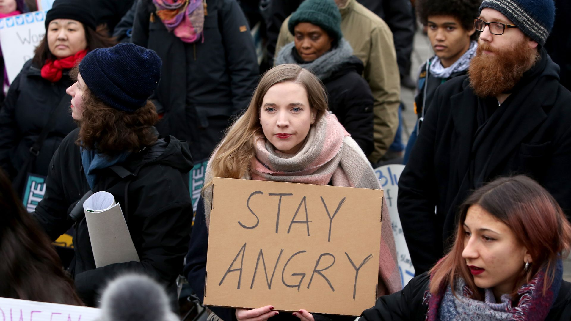 "A woman holds a sign that says ""Stay angry"""