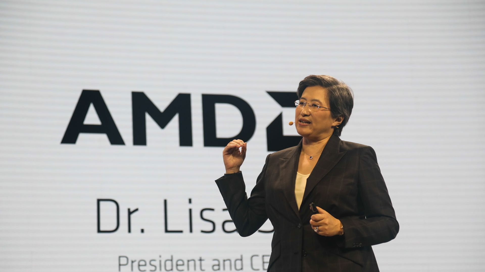 This image shows Su speaking on stage while wearing a blazer and microphone. The large screen behind her shows the AMD logo and her name.