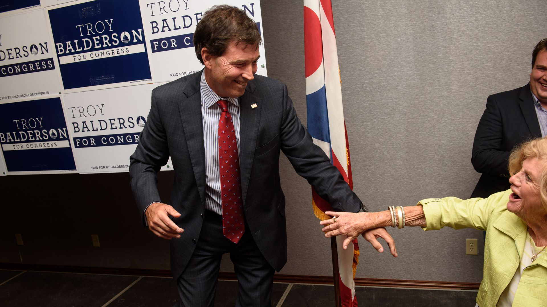 Republican Troy Balderson stepping down off a platform after giving a speech and smiling at a member in the crowd who is reaching out a hand toward him