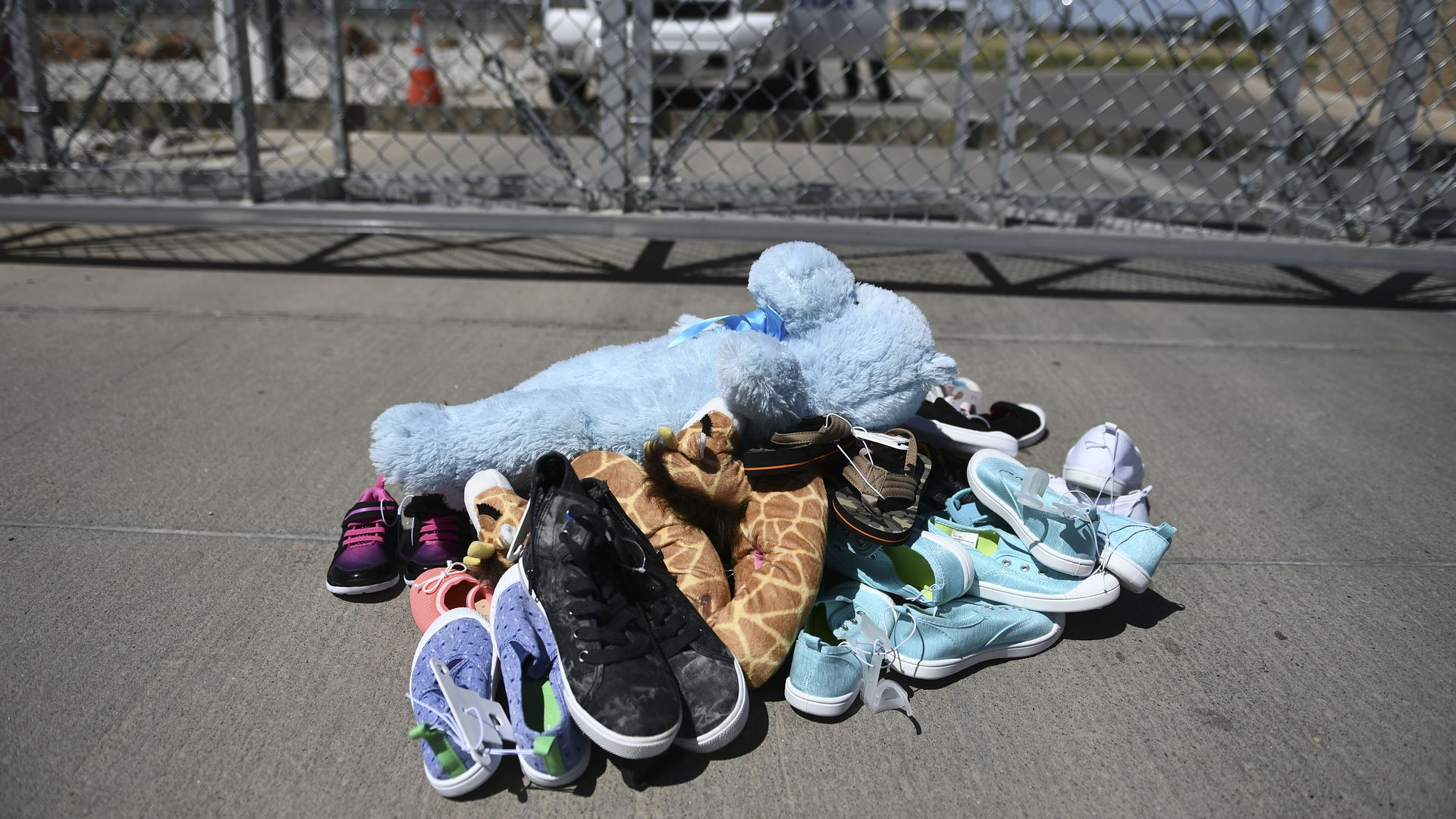 A pile of children's shoes and toys in front of a chain link fence at the border
